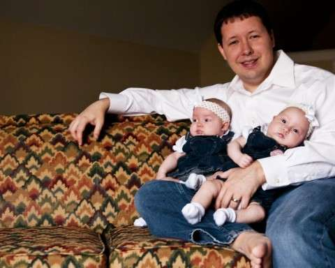 a man holding a twin babies