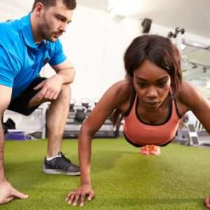 a girl doing push ups with an instructor