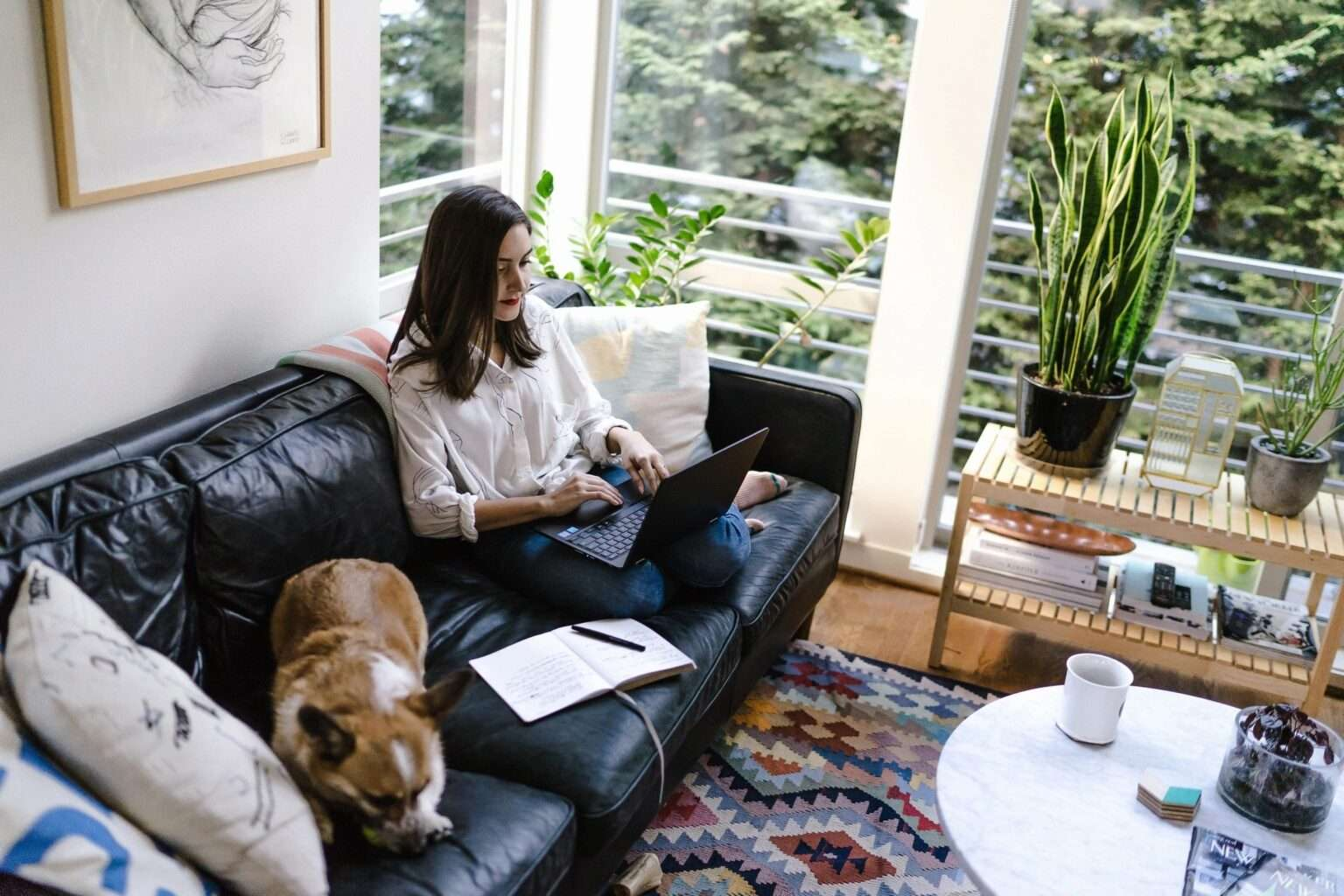 a girl and a dog sitting on the sofa in the living room
